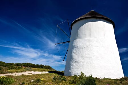 A path leading to a windmill with blue skies in the background and green grass in the foreground. Windmill shot taken from behind. Stock Photo - 6716550