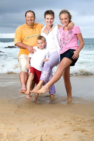 A happy family of mom, dad, sister and brother on the beach standing in wet sand with one leg and each putting their other leg together photo