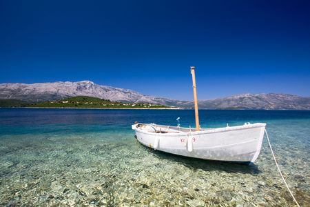 croatia: A small fishing boat tied into harbour on a beautiful sea