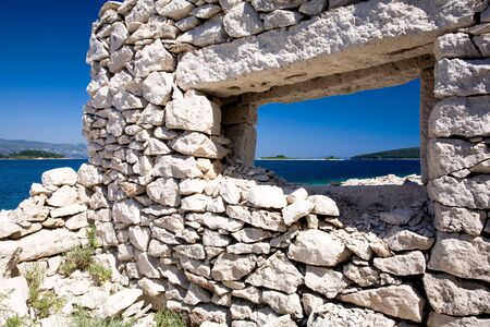 Old broken down house on the coast of Croatia with a view through the stone wall window. Stock Photo - 6716545