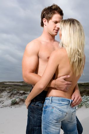 A topless man with his arms around a topless woman's waist while looking into her eyes on the beach photo
