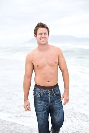 An attractive topless man  walking on the beach and smiling photo