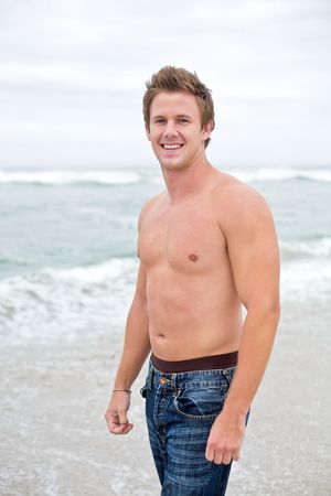 An attractive topless man looking towards camera smiling on the beach. photo