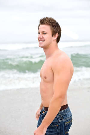 An attractive topless man looking off into the distance on the beach photo