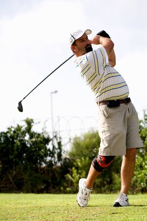 Male golfer teeing off with a injured knee wearing a knee brace.