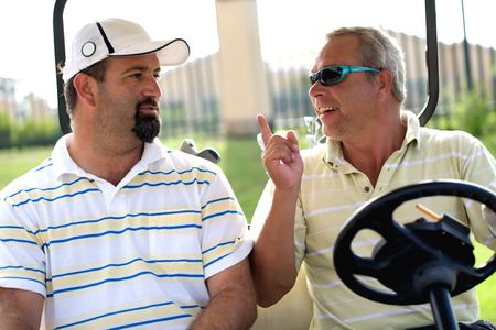 Two men in a golf cart argueing about the game.