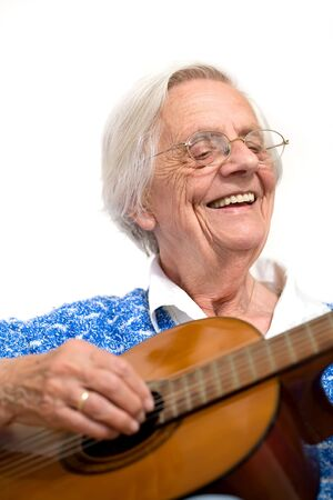 Elderly woman playing the guitar wearing a blue knitted top.