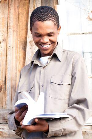 adolescentes estudiando: Amistoso estudiante negro paginar a trav�s de su libro.