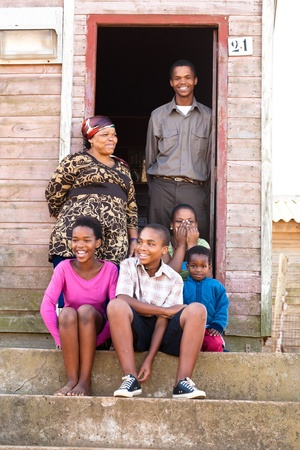 Cheerful black family on the steps infront of their rural house. Stock Photo