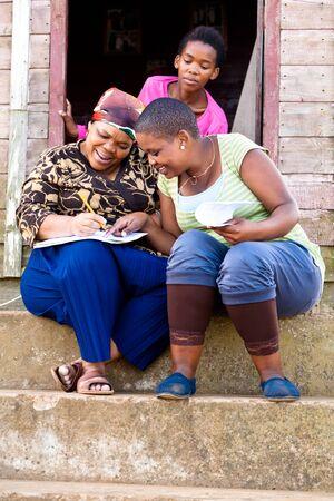 campi�a: Dos negro mujer rellenar un formulario mientras estaba sentado en pasos y stairing de un joven negro sobre sus hombros. Foto de archivo