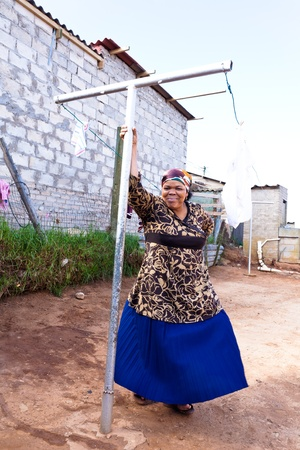 African black woman in traditional clothes standing against a outdoor washing line. photo