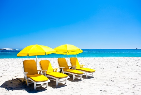 Four yellow beach chairs under two ubrellas on the beach.
