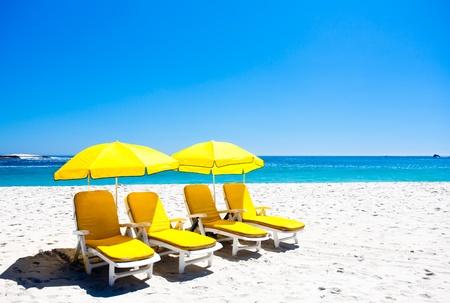 sun shade: Four yellow beach chairs under two ubrellas on the beach.