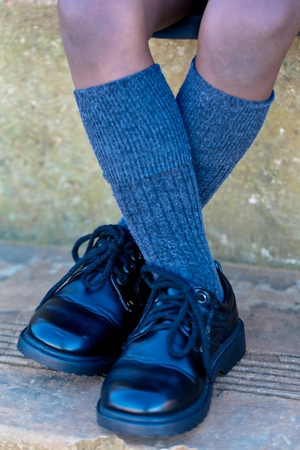 Close up shot of small black school shoes on a black kid wearing grey socks Stock Photo
