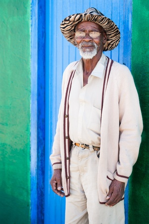 dirty old man: A old man standing in front of his colorful shack Stock Photo
