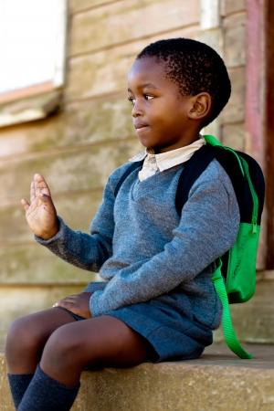 渡す人の手を振っている階段に座って小さな男の子