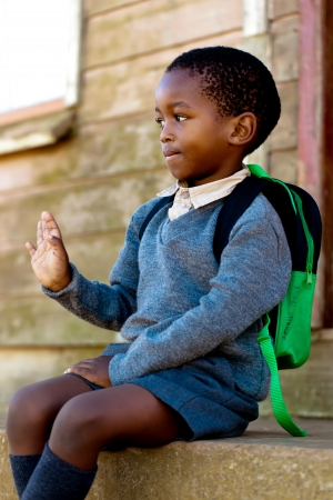 Small boy sitting on the steps waving for the people passing Stock Photo