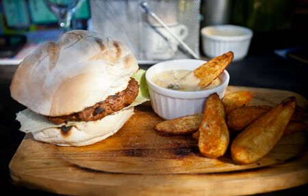 Steak burger with chips and mushroom sause photo