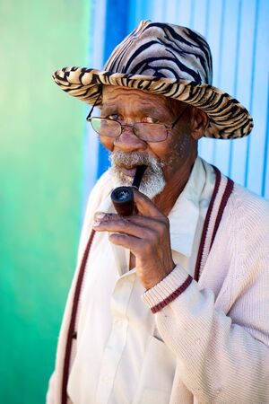 deprived: Old man sitting on his porch with his pipe in the hand