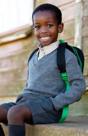 小さな男が学校に行く途中でバスを待っています。