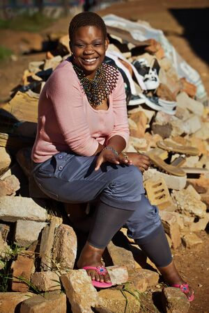 happy african woman: A young lady posing for the photographer on a load of bricks laying around.