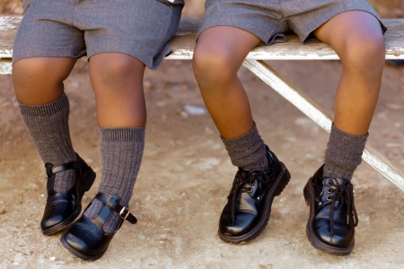 His and her school shoes, toughies on the step. Stock Photo