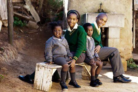 この家族の学校の子供たちが学校に向かう途中にバスを待っています。 写真素材