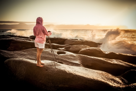 A girl taken pictures on the rocks at the ocean  photo