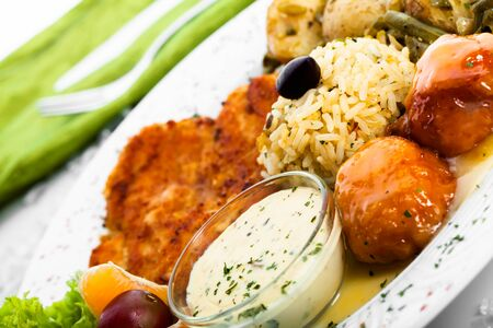 Chicken and rice being served with pumpkin cakes and potatoes  photo