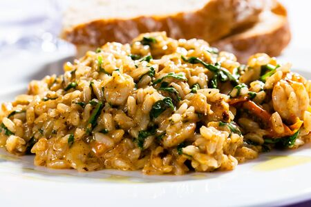 Risotto with spinach and bacon served with white bread  Stock Photo