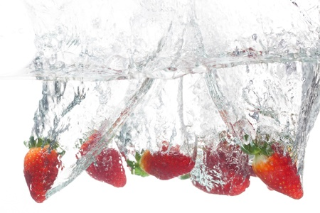 strawberry splash: Six strawberries is thrown into clear water in the tank