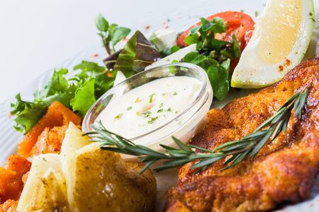 Potatoes and pumpkin is served with salad and cheese sauce  photo