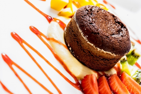 Chocolate souffle is served with strawberries and pineapples