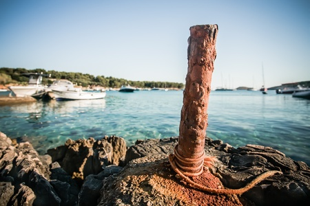 cement pole: A very old rusty anchor pole in the harbour of Hvar