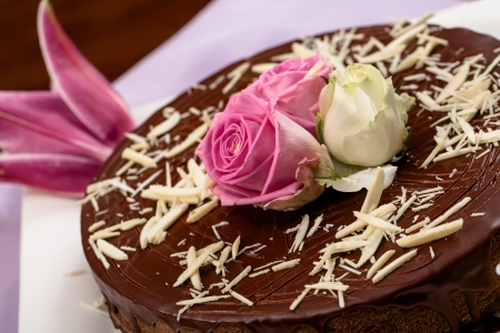 chocolaty: Choclate cake with white strips on top and roses also a lilly  Stock Photo