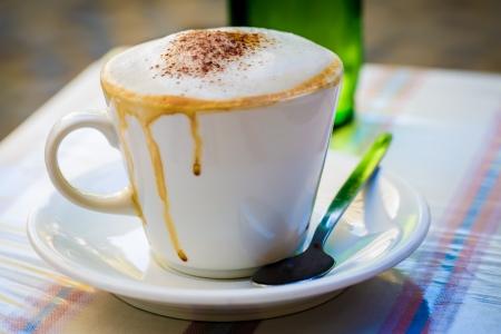 コーヒー カップがいっぱいコーヒーとミルクと、エッジの上を実行しています。