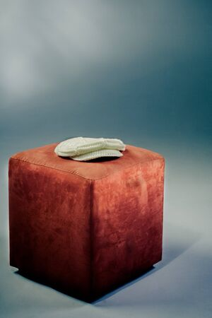 dunce cap: A white wool cap laying on a orange stool for art photography. Stock Photo