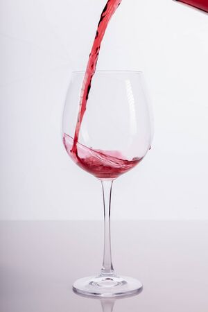 A glass of nred wine is being filled up from a bottle. photo