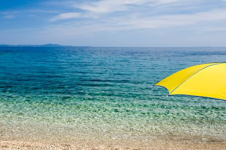 A shocking yellow umbrella looking over the crystal clear waters. photo