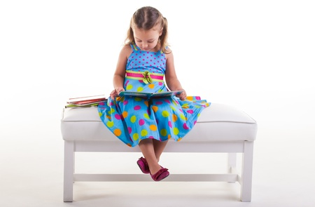 The little girl is sitting on the bench reading her books Stock Photo - 14563850