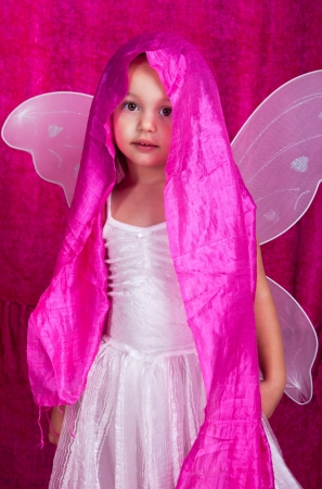 petti: Dressed in a white dress with wings and a pink drape around the head