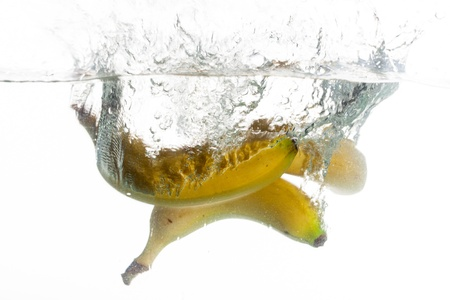 There are three yellow bananas thrown into clear water  photo