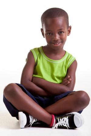 ni�os negros: El ni�o est� sentado con una gran sonrisa y tambi�n con los brazos cruzados y las piernas Foto de archivo