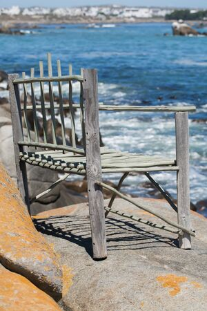 A beautiful wooden chair are on a situated on a rock. photo