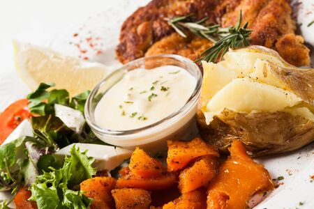 Chicken and rice being served with pumpkin and potatoes. photo