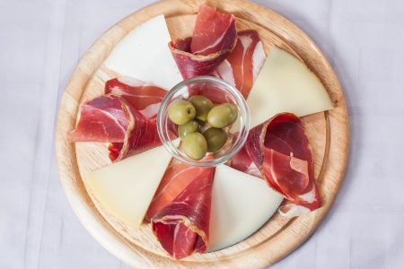 Cheese and bacon platter served with some olives. photo
