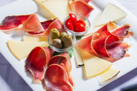 Cheese and bacon platter served with some olives and tomatoes.