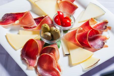 Käse und Speck Teller serviert mit einigen Oliven und Tomaten. Standard-Bild - 14940311