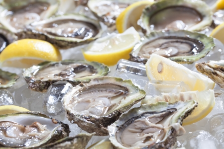 Oysters in a bowl with lemons.