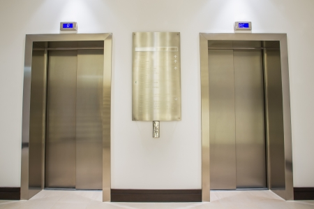 Two golden lifts situated on the ground floor of the company. photo